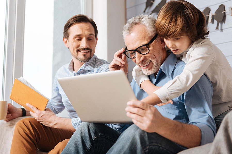 Blog - Grandfather and Grandson Hugging while Looking at Laptop with Father in Background
