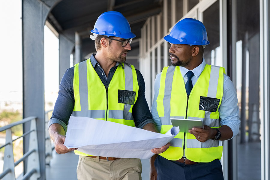 Business Insurance - Two Construction Men with Hard Hats Walking and Holding Papers