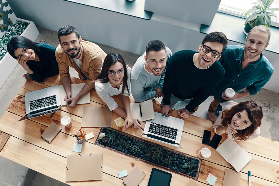 Employee Benefits - Team of Employees Looking up and Smiling in Office
