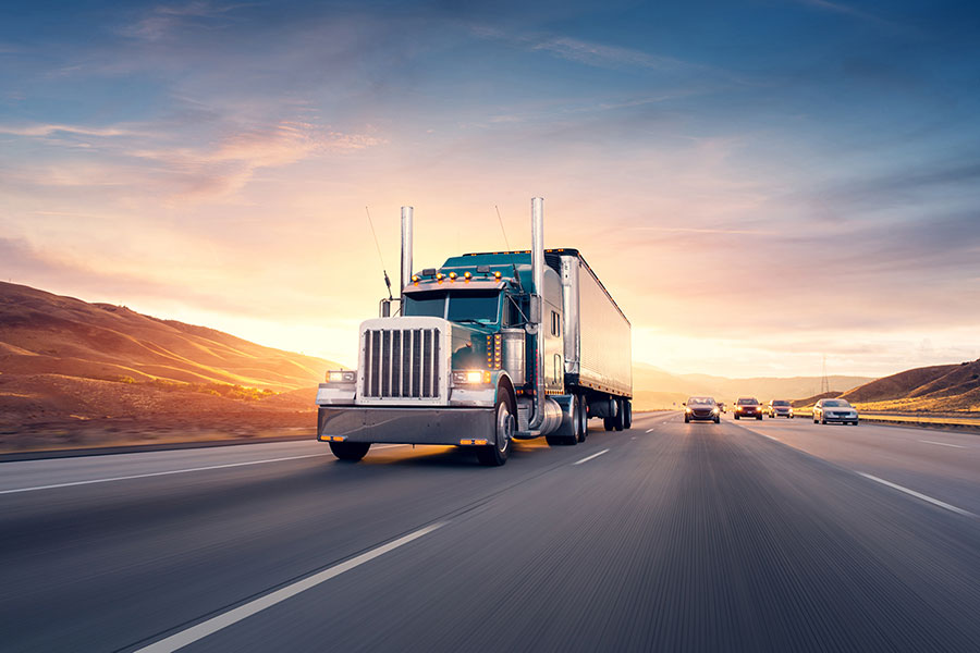 Risc - Tractor Trailer Truck Driving Down Highway with Sunset in Background